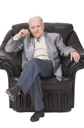 Portrait of a senior man sitting in an armchair and thinking deeply.Shot with Canon 70-200mm f/2.8L IS USM