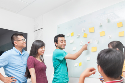 Asian business people team drawing on white wall whiteboard with sticky notes creative real office