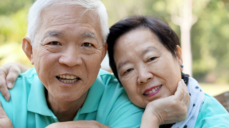 close up potrait of Asian senior couple on bright green background