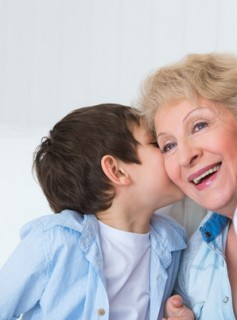 Grandmother with grandson having fun at home - whispering secret
