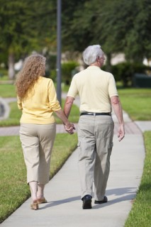 Rear View Senior Man and Woman Couple Walking Holding Hands