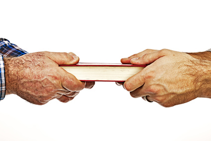 Closeup of mature man´s hand giving a book to his son,conceptual image, over white background