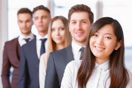 Team in the office. Asian businesswoman standing in the foreground smiling, her team of co-workers in the background