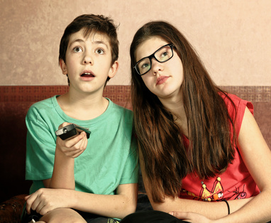 teen siblings brother and sister watching tv close up indoors portrait with remote control